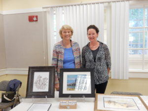 Art Show committee members Jeanne Reidy and Sue Iozzo stand with silent auction items